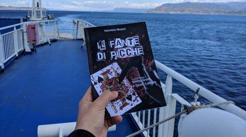 Il libro Il fante di picche tenuto in mano a bordo di una nave